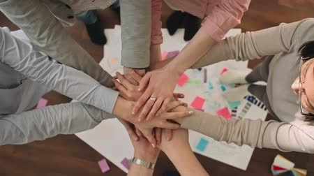 birlik : Top view close-up of young business team stacking hands together showing unity after brainstorming, shot on Sony NEX 700 Stok Video