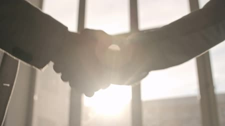 partnerstwo : Close-up of two businessmen shaking hands in sunlight
