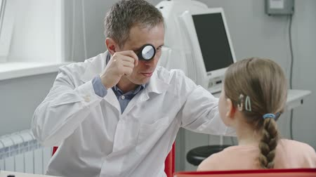 Eye doctor in white medical gown using indirect ophthalmoscope and lens to examine eyes of little girl and giving her advice