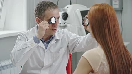 vizyon : Optometrist in white gown examining eyes of female patient using indirect ophthalmoscope and lens and giving her medical advice