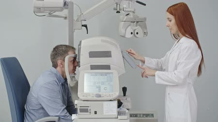 Female optometrist using modern automatic refractometer for refraction test during eye examination