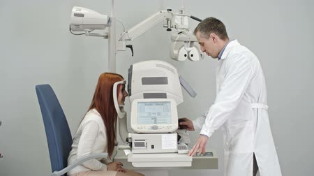 Optometrist using modern automatic refractometer to measure eye refraction of female patient during eye examination Wideo