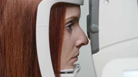 Closeup of young red-haired woman having eye refraction test during routine eye examination