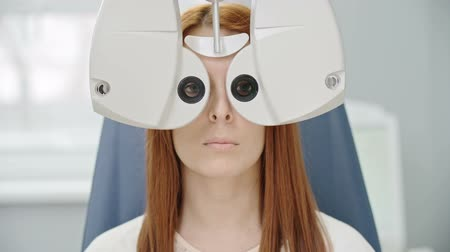 Closeup of young red-haired woman reading eye chart during distance vision test with modern automated phoropter