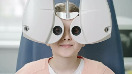 Closeup of little girl reading eye chart during distance vision exam with modern automated phoropter and then smiling at camera 影像素材