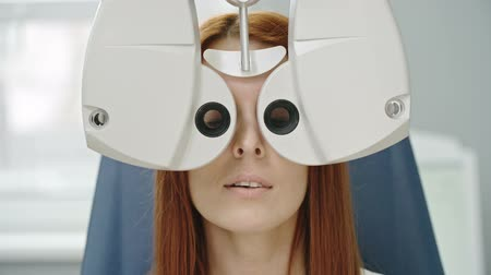 Closeup of young red-haired woman reading eye chart during distance vision exam with modern automated phoropter Wideo