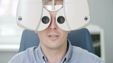 Closeup of mid adult man reading eye chart during distance vision exam with modern digital phoropter