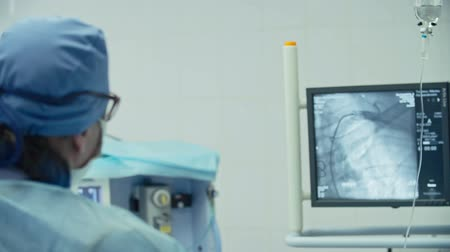 przeszczep : Over the shoulder view of cardiac surgeon looking at monitors while performing coronary artery bypass surgery in modern operating room Wideo
