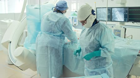 przeszczep : Surgeon looking at monitors while performing coronary artery bypass surgery assisted by nurse in modern operating room