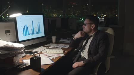 идущий : Tracking medium shot of exhausted businessman analyzing financial statistics on computer screen in dark office, taking off his glasses