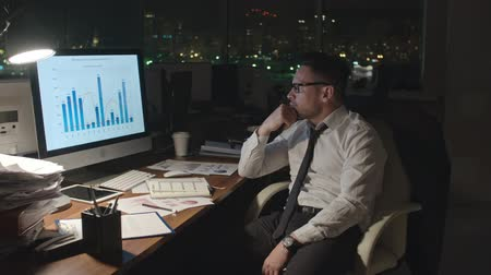 financial : Tracking medium shot of exhausted businessman analyzing financial graphs on computer screen in dark office, taking off his glasses Stock Footage