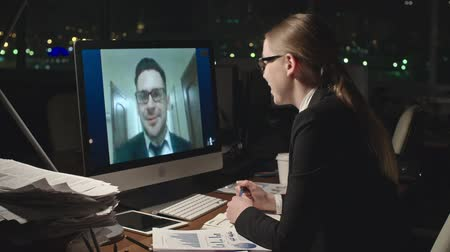 bate papo : Panning medium shot of young businesswoman talking with male colleague through video call on computer and making notes in her notebook in dark office late at night