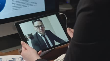 bate papo : Closeup of businesswoman holding tablet computer during video call with male business partner showing her documents with financial data