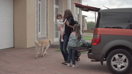 levou : Mom and her little daughters taking their stuff from trunk of the car while their cute lab walking around them