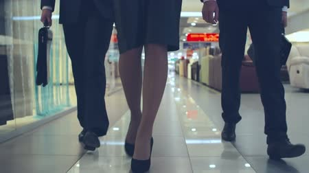 oblek : Close up of legs of businesswoman and her two male colleagues walking on the floor of shopping mall towards the camera