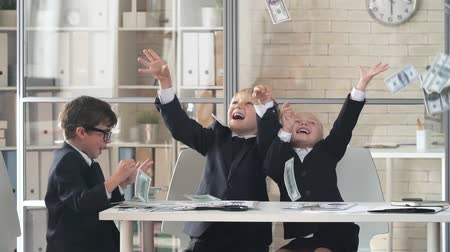 bogaty : Little girl and two boys in business suit tossing money and laughing in the office