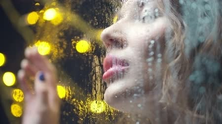 темно : Close up of sad girl looking away and leaving kiss on wet window