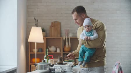 confecção : Father holding his lovely baby boy and making morning coffee