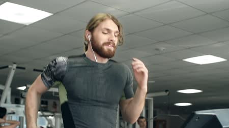 sluch : Young man running on treadmill and listening to music on headphones