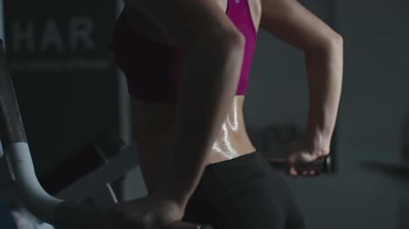 Side view of sweating woman doing dips on parallel bar in gym in slow motion
