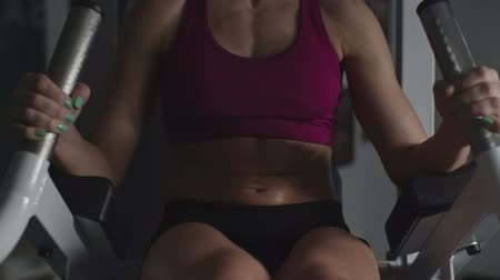 Midsection of woman with tanned stomach sweating while doing l-sits in the gym