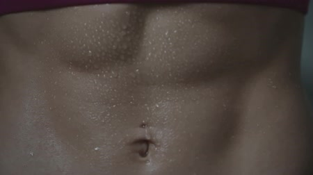 abs : Close up of tanned wet female stomach with strong abdominal muscle