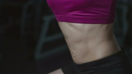 Midsection of woman with perfect abs hanging on pullup bar and doing crunches with knee raise 影像素材