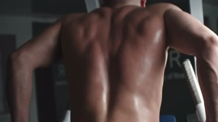 Rear view of man doing parallel bar dip exercise in the gym 影像素材