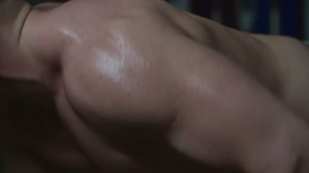 Close up of male arm with massive bicep doing arm exercise in the gym