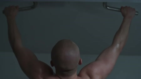 Rear view of muscular shirtless man doing pull ups on bar in the gym
