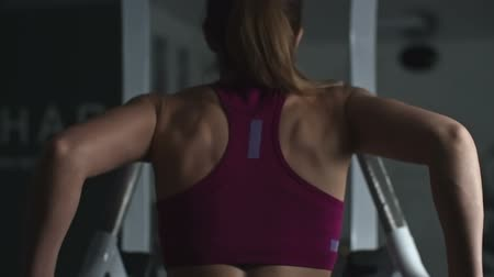 Rear view of woman in sport bra doing dips on parallel bars in slow motion