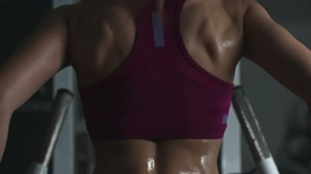Rear view of woman with sweaty muscular back doing dips on parallel bars in slow motion Wideo