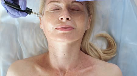 Directly above view of relaxed woman with closed eyes lying on couch during doctor doing anti-aging treatment with apparatus