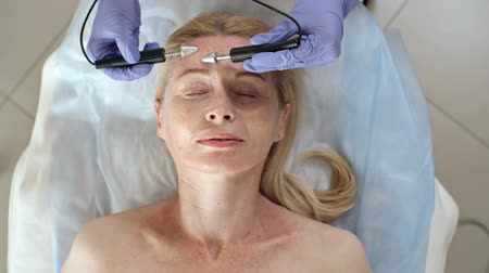 Directly above view of mature woman with closed eyes getting anti-aging treatment with apparatus