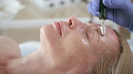 Closeup of face of woman with wrinkles lying with closed eyes while beautician making her anti-aging procedure