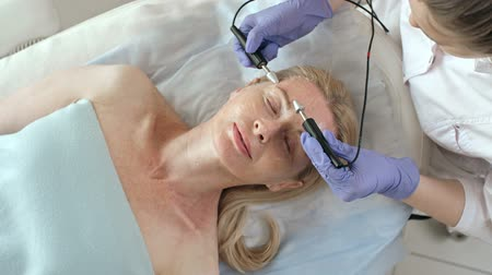 Top view of mature woman lying on couch in cosmetology cabinet while professional beautician doing therapy for her face