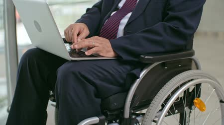 Disabled businessman sitting in wheelchair and using laptop Wideo