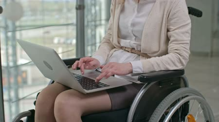 Woman typing on her laptop while sitting in wheelchair in the office center Wideo