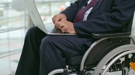 Midsection of businessman sitting in wheelchair and working on his modern laptop