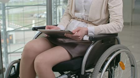 Businesswoman with disability sitting in wheelchair and using digital tablet