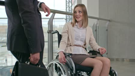 Woman in wheelchair talking to businessman standing in the corridor in modern office building Wideo