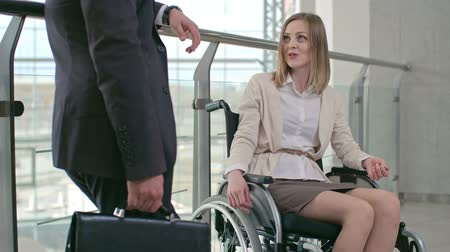 Young attractive woman sitting in wheelchair telling about something her business partner in the corridor of office center Wideo