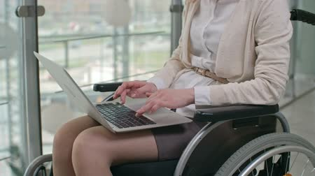 Business woman in wheelchair working on her modern laptop