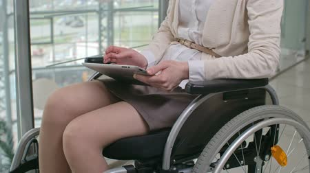 Woman sitting in wheelchair and working on her tablet in the corridor of business center