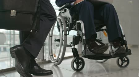 Legs of businessman standing with briefcase in the corridor of office building next to his disabled colleague sitting in wheelchair and using his laptop 影像素材