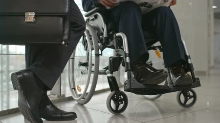 Legs of businessman standing with briefcase in the corridor of office building next to his disabled colleague sitting in wheelchair and reading newspaper