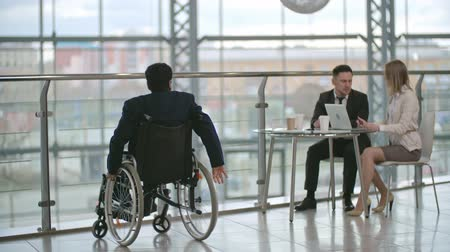 Disabled businessman sitting on wheelchair and talking on the phone; man and woman sitting at the glass table with laptop and talking