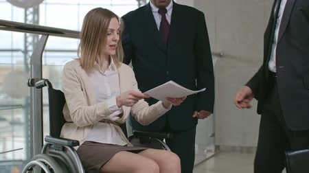 Businesswoman sitting in wheelchair and her colleague standing next to her, she greeting her business partner with handshake, giving him documents and talking to him Wideo