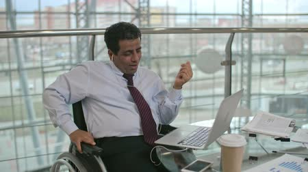 Businessman sitting on wheelchair and having video call on laptop then putting off earphones and start typing