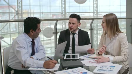 Two businessmen and businesswoman having a meeting in the office: they sitting at the table with financial documents, laptop and tablet on it and talking Wideo